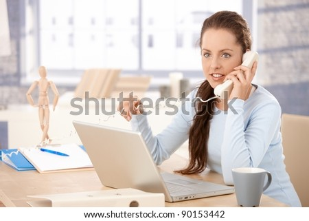 Attractive young femalel working on laptop in bright office, talking on phone.?