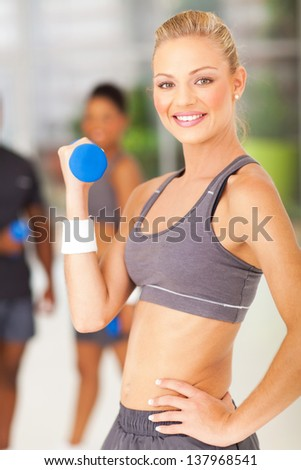 attractive young fit woman lifting dumbbell - stock photo