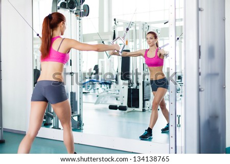 Attractive young fitness model works out on training apparatus inside in fitness center - stock photo
