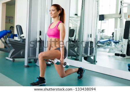 Attractive young fitness model works out with dumbbells in fitness center