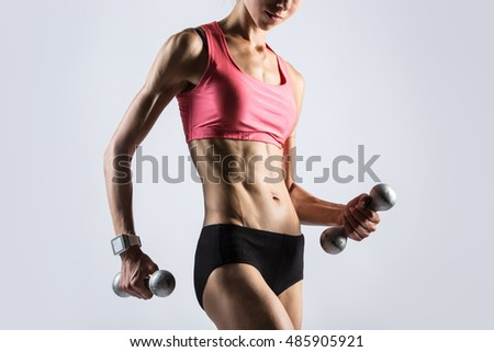 Attractive young fitness person wearing smartwatch and red sportswear top lifting dumbbells. Serious sporty model girl working out, doing weight training with dumbbells on grey background. Close-up