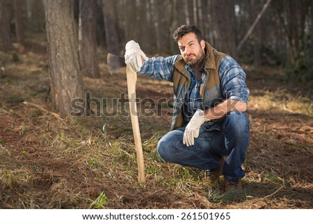 Attractive young forestry worker leaning on the axe, posing in the woods - stock photo