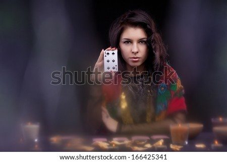 Attractive young fortune teller holdin card - stock photo