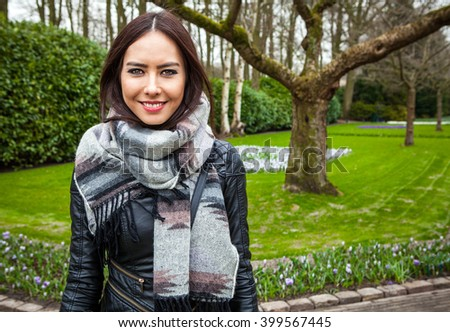 Attractive young friendly woman with long beautiful hairs posing in park.