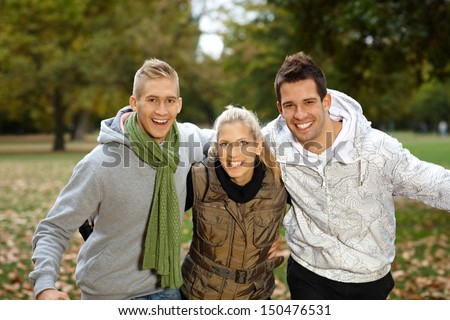 Attractive young friends having fun in autumn park, smiling, looking at camera. - stock photo