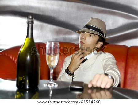 Attractive young gangster drinking in cocktail party at cabaret - stock photo