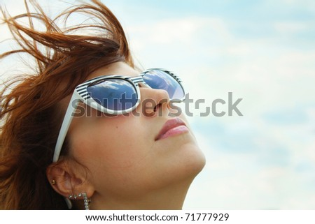 attractive young girl against the blue sky in a  sunglasses