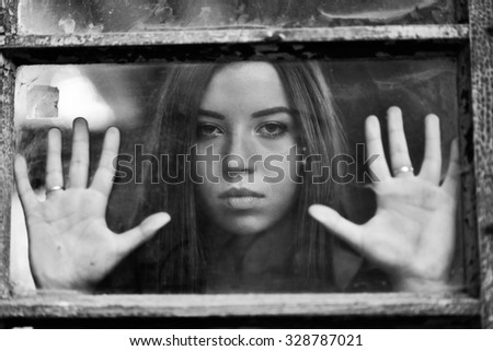 Attractive young girl behind the window of abandoned house - stock photo