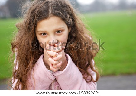 Attractive young girl being thoughtful while sitting on a bench in a park and blowing into her hands to warm up during a cold winter day, outdoors. - stock photo