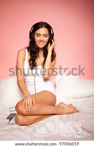 Attractive young girl curled up on her bed wearing headphones and with a gentle smile as she listens to music - stock photo