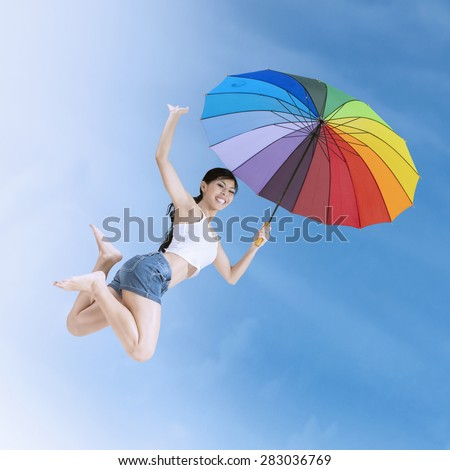 Attractive young girl enjoy summer holiday and jumps with a colorful umbrella under clear sky - stock photo