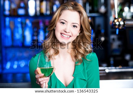 Attractive young girl enjoying champagne in a pub.