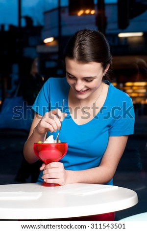 Attractive young girl enjoying ice cream with toppings - stock photo