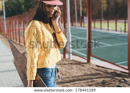 Attractive young girl hipster posing by the wall. Not isolated. Indoor - stock photo