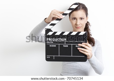 Attractive young girl holding clapper board front of her face. - stock photo