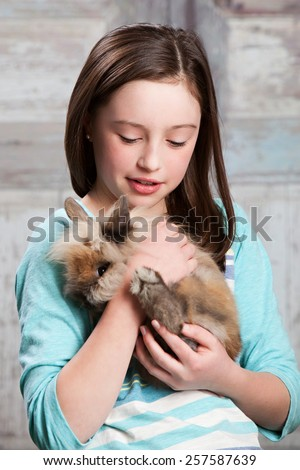 Attractive young girl hugging her pet bunny.