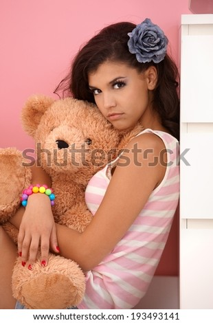 Attractive young girl hugging toy bear, looking at camera. - stock photo