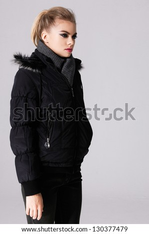 attractive young girl in black jacket standing against gray background - stock photo