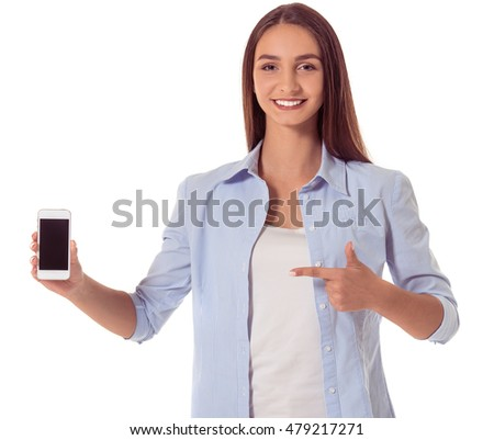 Attractive young girl in casual clothes is holding a smartphone, pointing on it, looking at camera and smiling, isolated on white background