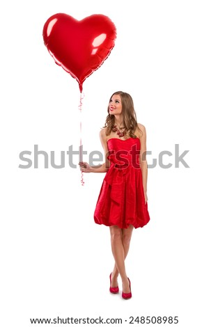 Attractive young girl in red dress holding Valentine's Day helium balloon - stock photo