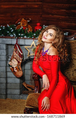 Attractive young girl in red dress sitting in armchair near fireplaces Christmas - stock photo