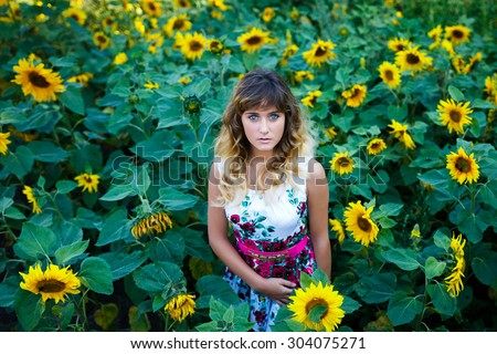 Attractive young girl in the field of sunflowers at summer time - stock photo