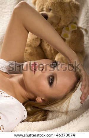 Attractive young girl is lying on the white counterpane - stock photo