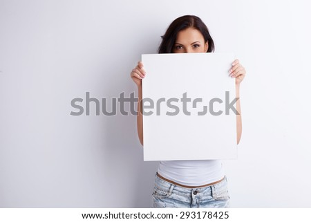Attractive young girl is showing a white square. It closes half of her face. She looking forward confidently. Isolated on white and copy space on right - stock photo
