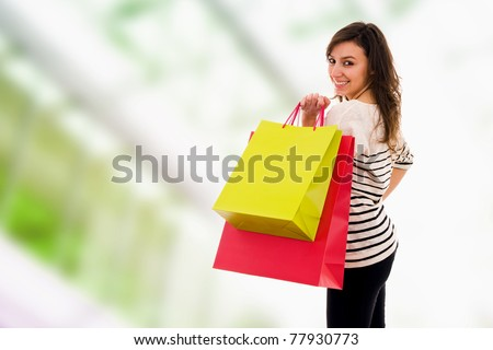 Attractive young girl looks and smiles through a shoulder holding in hands multi-coloured bags at the shopping - stock photo