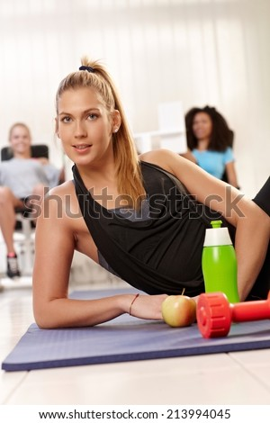 Attractive young girl lying on side at the gym, water, dumbbell and apple front of her. - stock photo