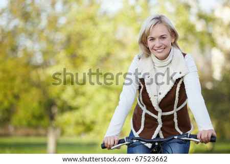 Attractive young girl on a bicycle in the park - stock photo