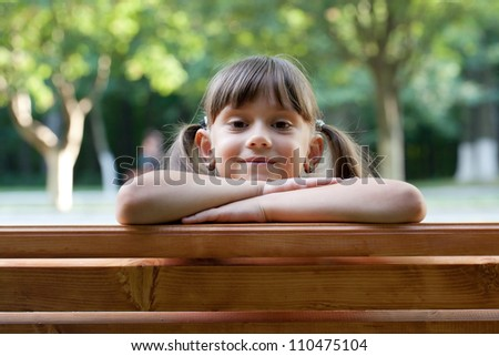 Attractive young girl on a park bench