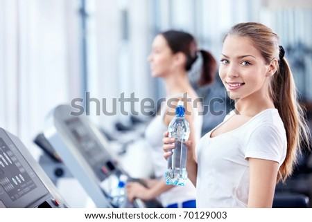 Attractive young girl on a treadmill in fitness club - stock photo