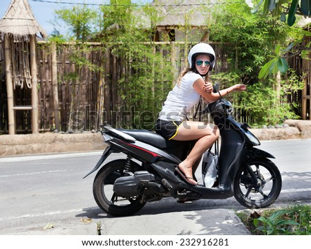 Attractive young girl on scooter stopped on the road - stock photo
