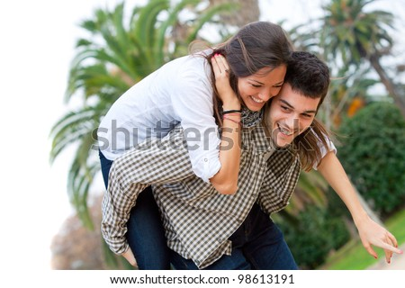 Attractive young girl piggybacking on boyfriend outdoors. - stock photo