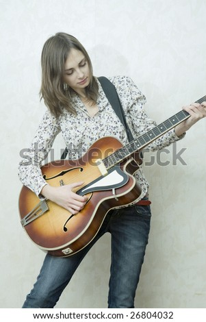 Attractive young girl playing guitar. Cowgirl - stock photo