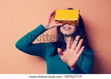 Attractive young girl playing video game with cardboard virtual reality headset. Trending technology and hipster colors. - stock photo