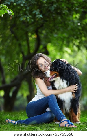 Attractive young girl playing with dog - stock photo