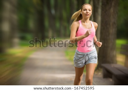 Attractive young girl running in park