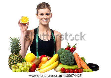 Attractive young girl showing sliced orange, fruits and vegetables around her. - stock photo