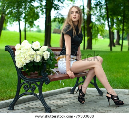attractive young girl sitting on a bench in a large bouquet of white roses - stock photo