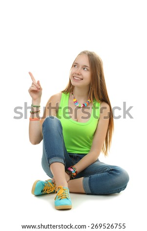 Attractive young girl sitting on floor pointing with finger - stock photo