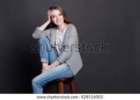 Attractive young girl sitting on high wooden chair. She smiles sincerely. She is smart and lovely, she is dressed in a gray sweater, white T-shirt and blue jeans. She has beautiful blonde hair. - stock photo