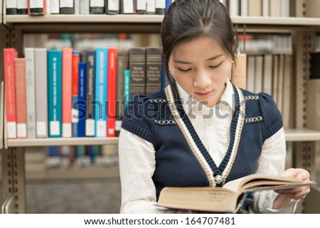Attractive young girl sitting on the floor in front of a bookshelf reading a thick old book