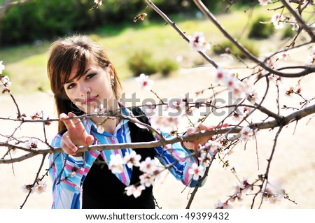 attractive young girl standing with first spring flowers of sakura