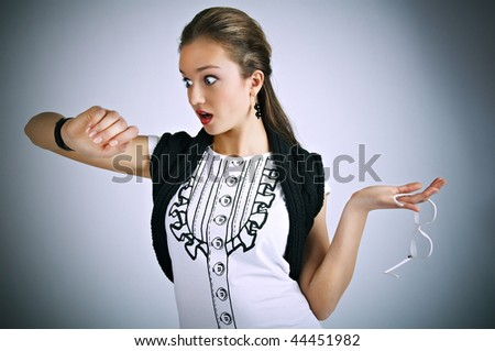 Attractive young girl surprised by time - stock photo