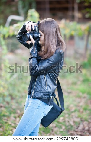 Attractive young girl taking pictures outdoors. Cute teenage girl in blue jeans and black leather jacket taking photos in autumnal park. Outdoor portrait of pretty teen having fun in park with camera - stock photo