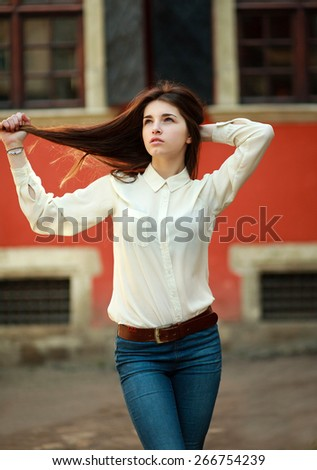 Attractive young girl walking on street of the old city summer day - stock photo