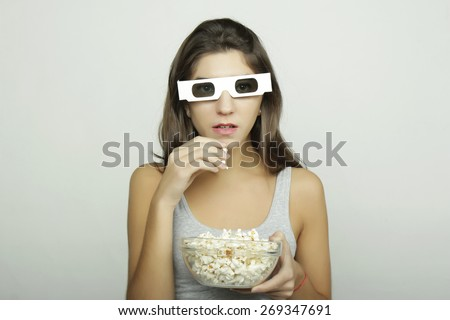 Attractive young girl watching a movie with popcorn and 3D glasses. Cinema concept - stock photo