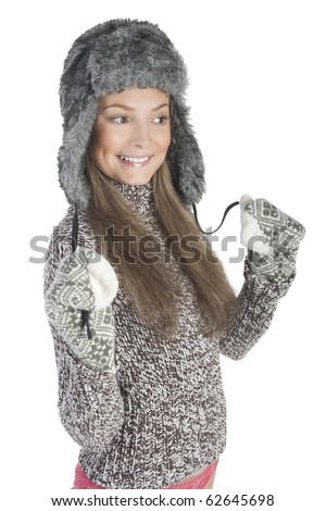 Attractive young girl wearing a warm sweater, fur hat and mittens - stock photo